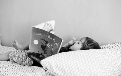 Boy reading book picking his nose