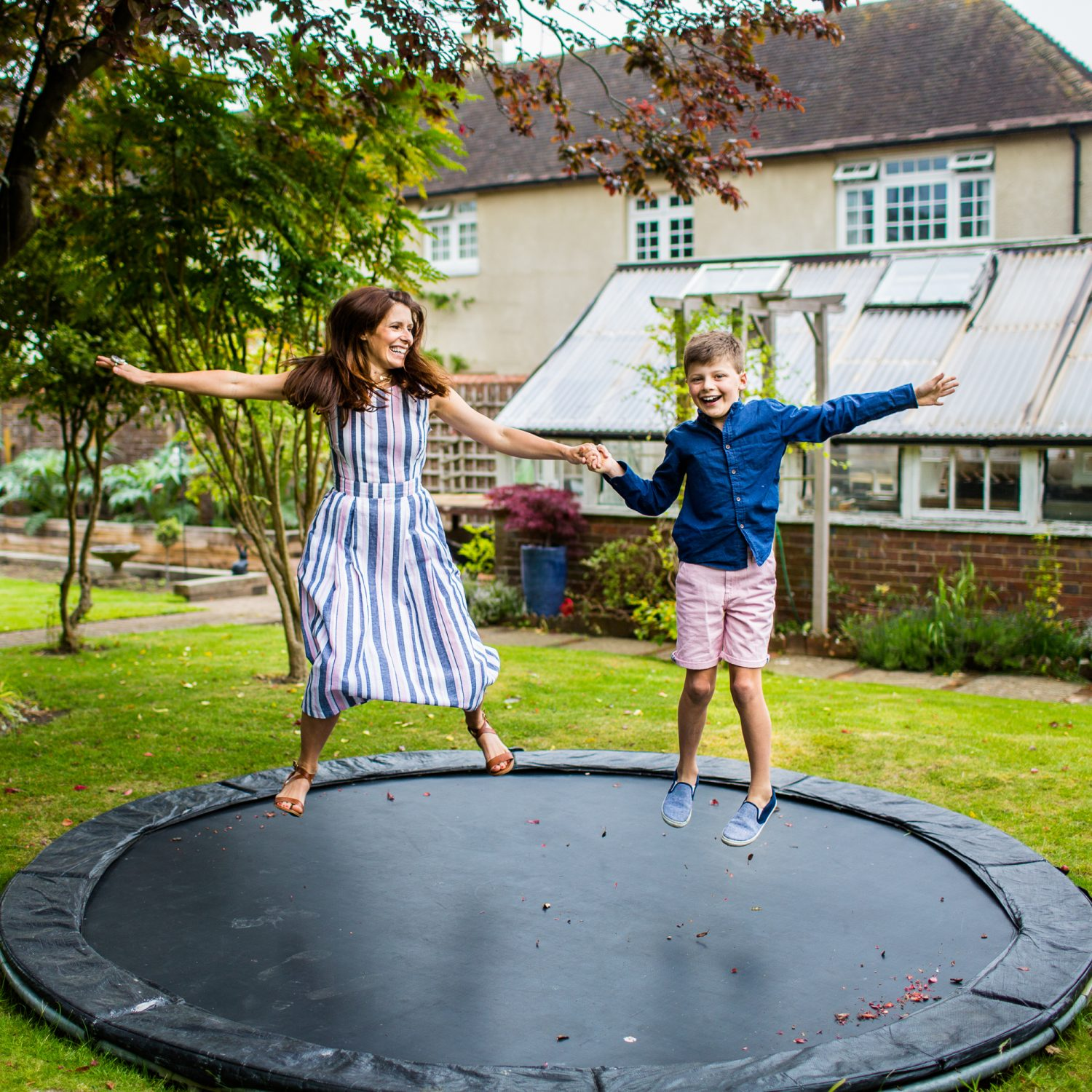 Documentary Family Photographers : Mother and son jumping on the trampoline