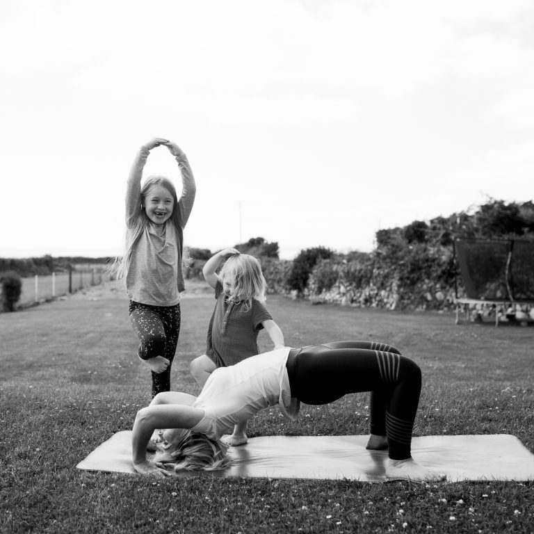 Documentary Family Photographers : Mother and daughters doing yoga together in the garden, Dublin