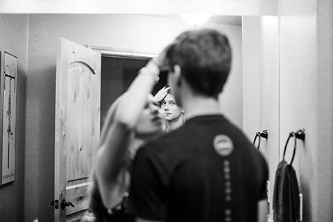 Documentary Photograph of teen girl straightening a teen boy's hair