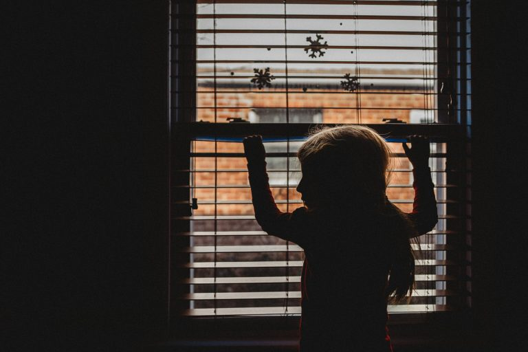 Documentary family photography: A young girl stands in silhouette by a window. Long Island, NY.