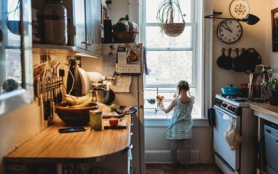 Documentary Family Photography: A young girl looks out her kitchen window. Queens, NY.