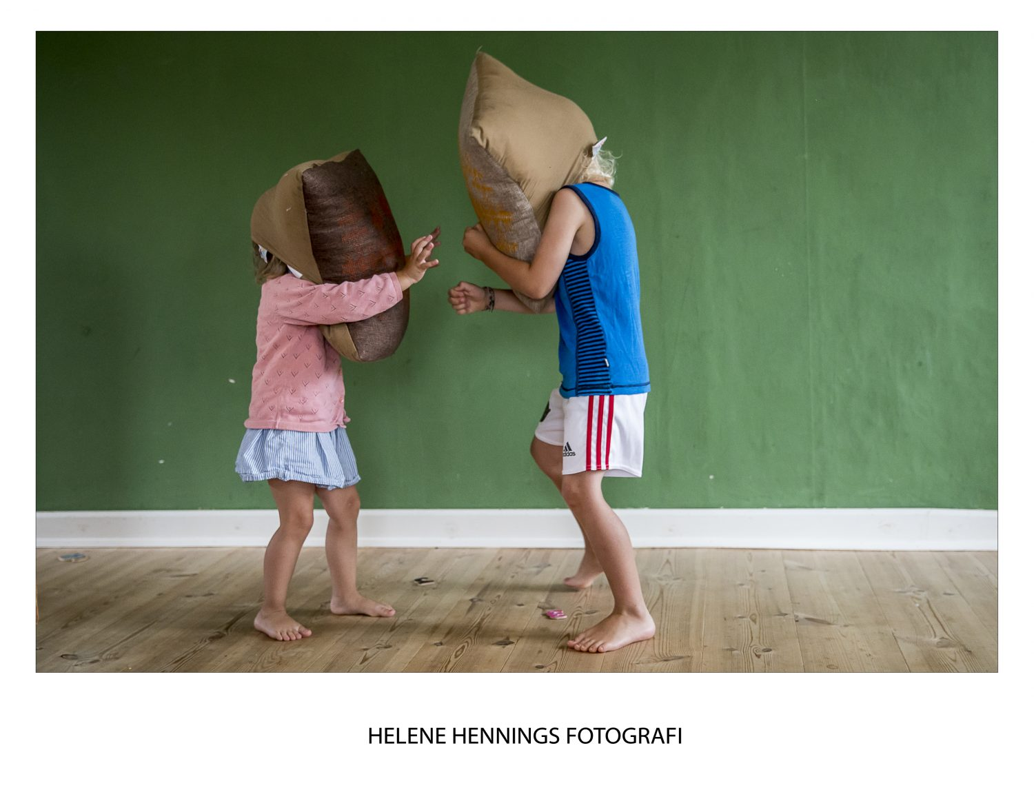 siblings play zombies with pillows on their heads