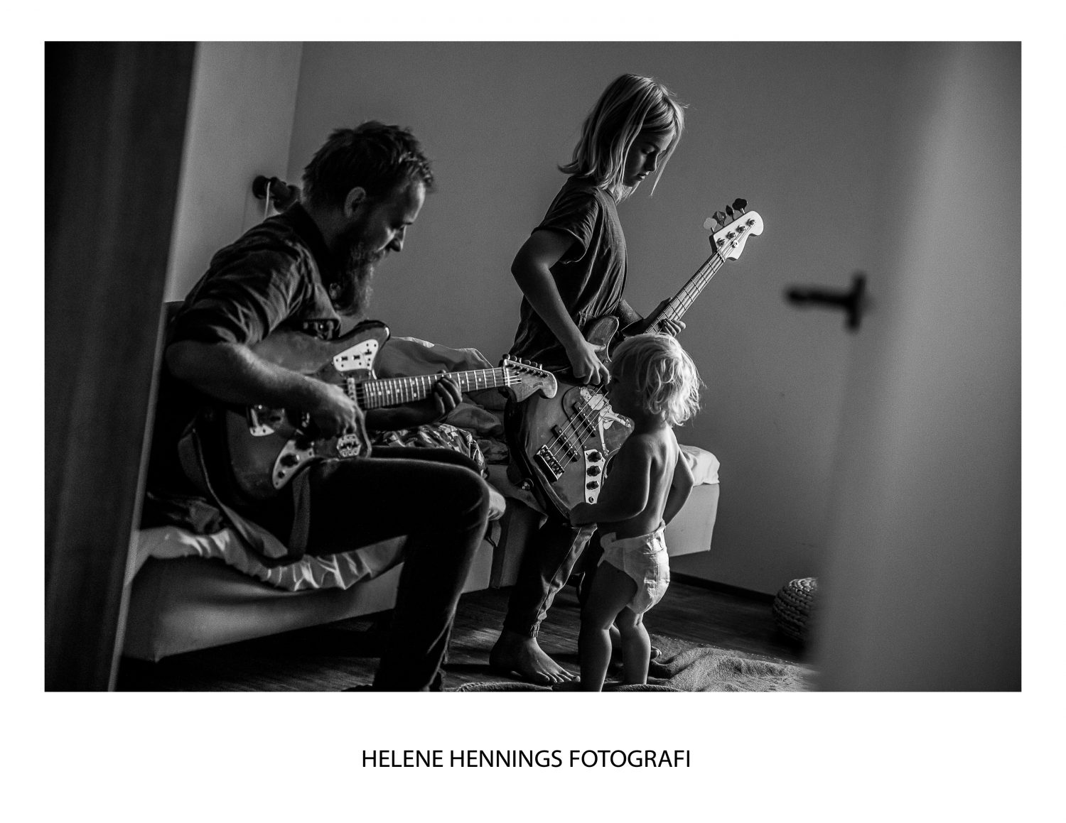 a father and his sons plays guitar and bass