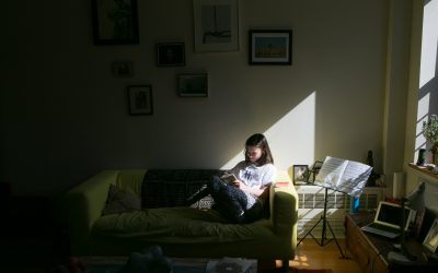 Documentary Family Photography: Pre-teen reading with a stream of light coming in the window. New York, NY USA