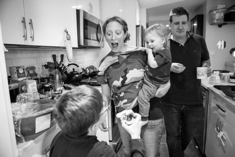 Documentary Family Photography: Mother holding son having fun in the kitchen. New York, NY USA