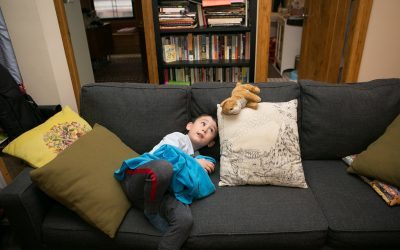 Documentary Family Photography: Boy playing on a couch with his stuffed animal. New York, NY USA