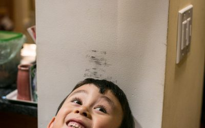 Documentary Family Photography: 5 year old boy next to a measurement wall. New York, NY USA