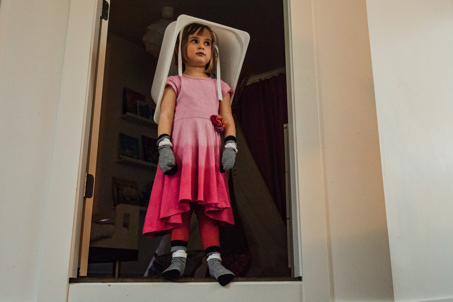 girl in pink dress with bucket on head and socks on hands