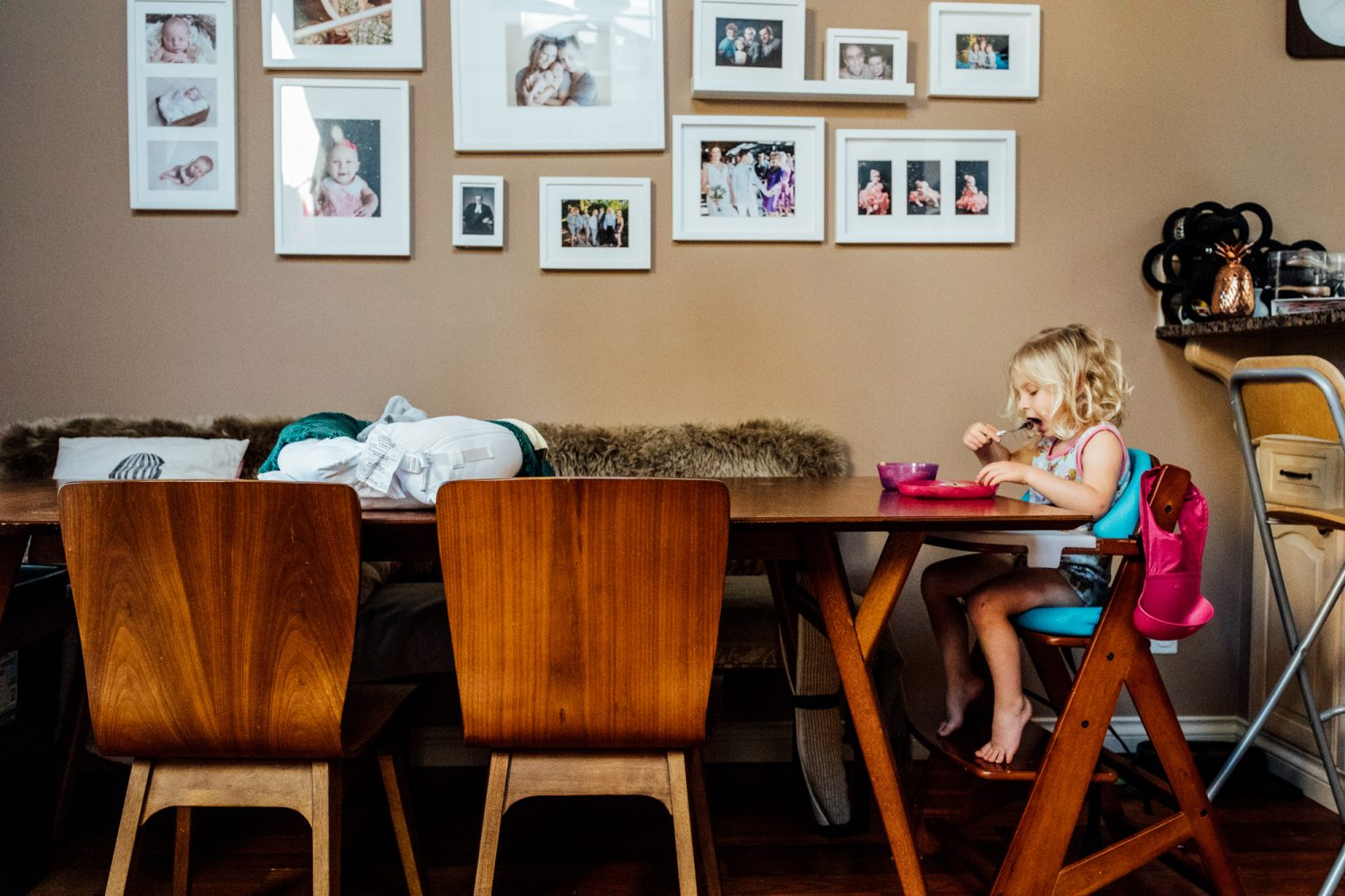 young girl eats pancakes at table alone