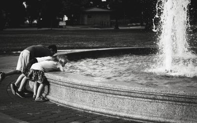 three unknown children reaching into the water of an outdoor fountain at RIverside park.