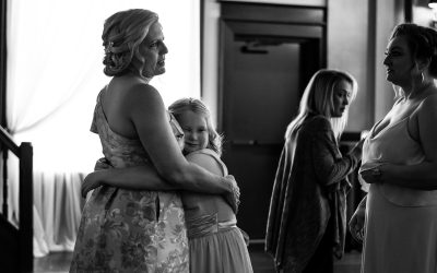 Granddaughters face scrunched up into Grandmas stomach as she gives her a bear hug at a wedding.