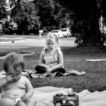 Daughter sitting in middle of the yard with a scowl on her face, while brother is covering his eyes.