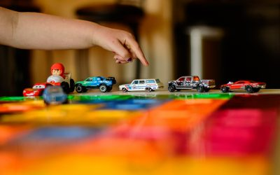 childs finger posed over hot wheels cars that are lined up on a colorful surface.