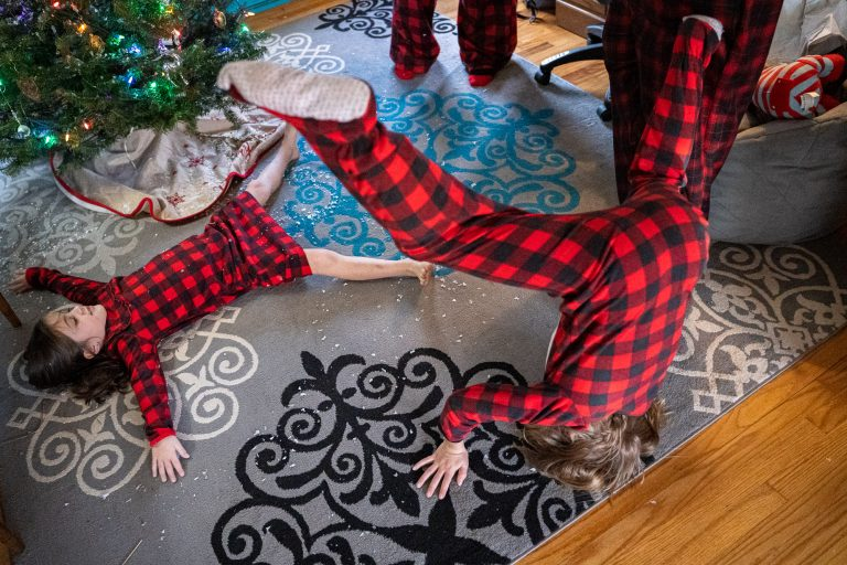 Kids at Christmas time!! After decorating the tree with fake snow, one girl lays on the carpet to make a snow angel while the other does a headstand.