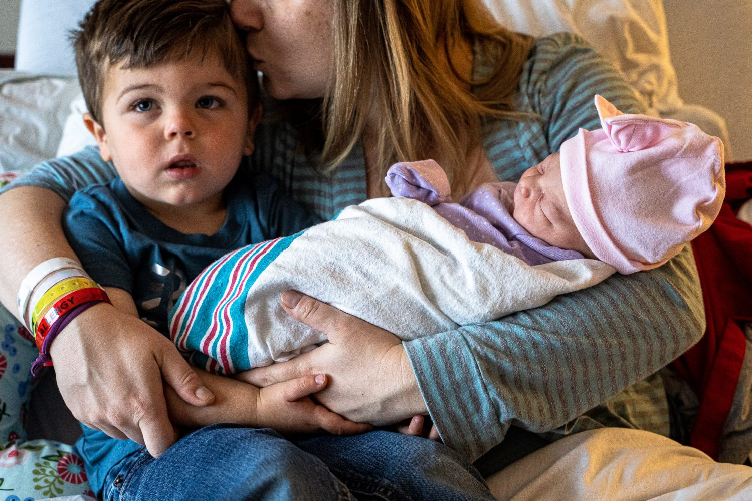 Love triangle - new big brother multitasks, helping hold his new baby sister while watching TV; mom holds both in her arms while planting a kiss on h er son's head.