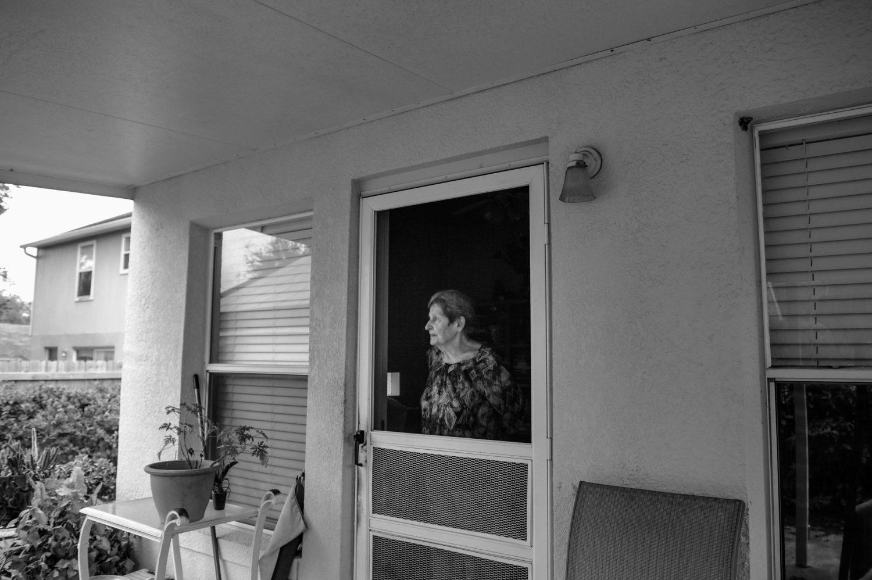 elderly woman stares out porch door