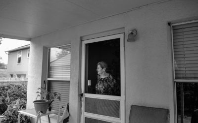 elderly woman stares out porch door