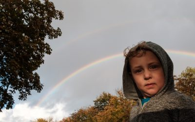 Boy looking intently forwards with rainbow behind