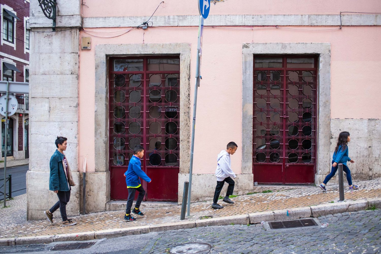 Kids walking up a hill in Lisbon