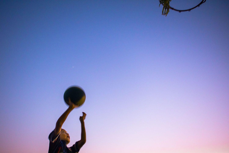 Boy playing basketball before a beautiful sky